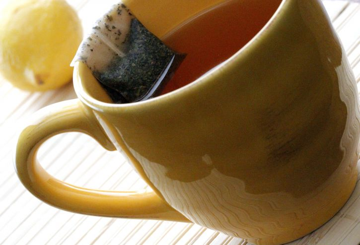 yellow, ceramic, cup, contained, hot, water, resting, rim, steeping, tea, bag