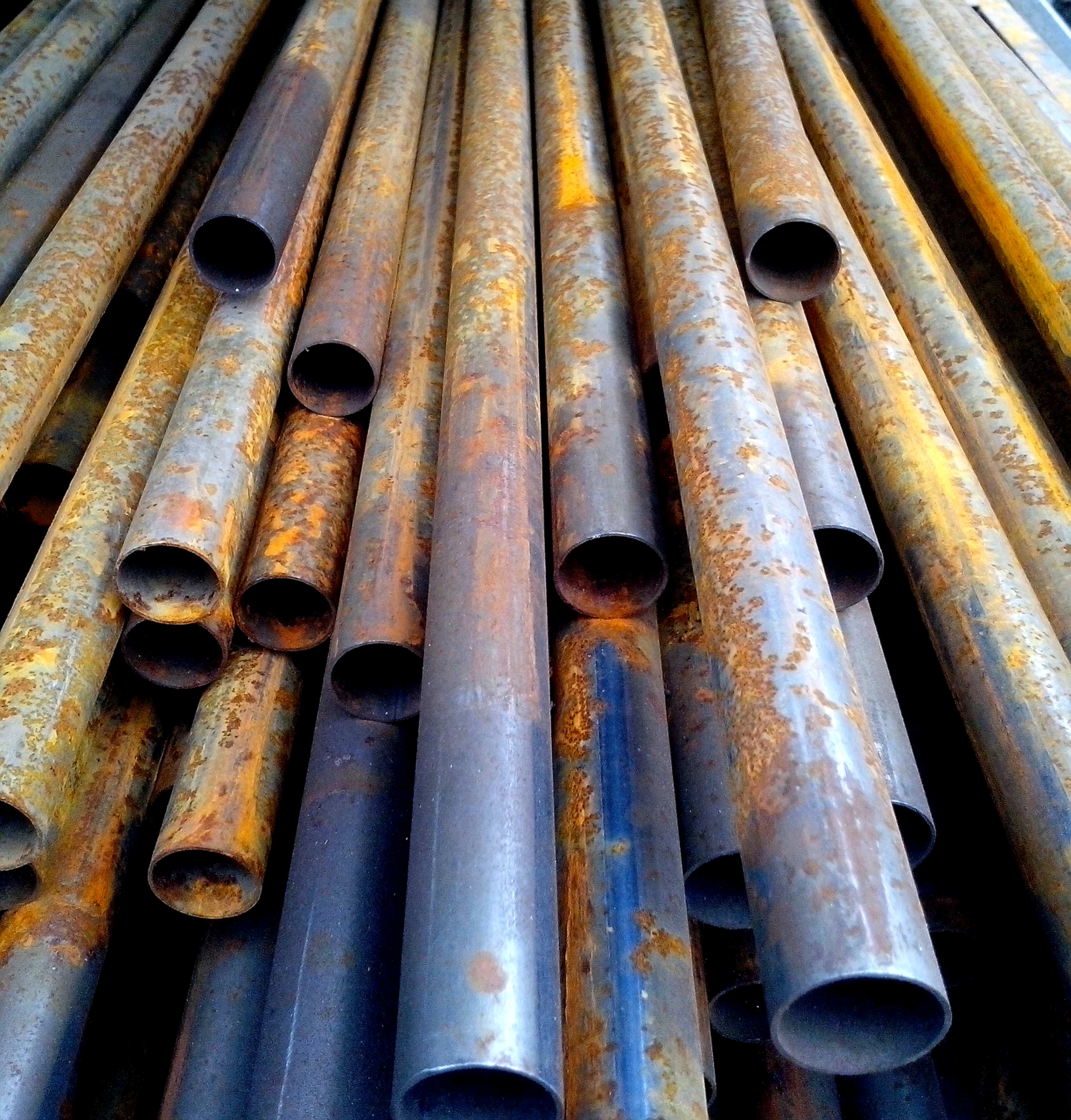 Free photograph; rusty, round, metal, pipes, stacked