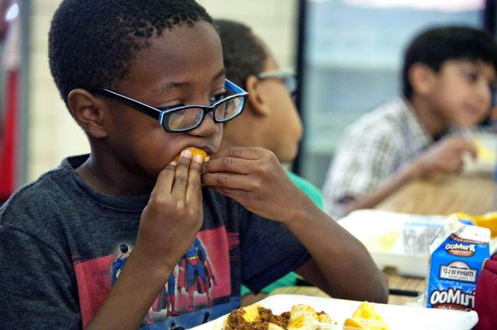 African American, boy, photographed, eating, freshly, peeled, orange
