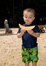 garçon, tenue, tranche, cantaloup, mains, debout, plage, sable