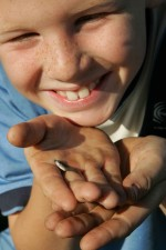 up-close, face, young boy, holds, small, fish, hand