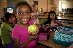 smile, young, African American, girl, holding, Granny Smith apple, hand