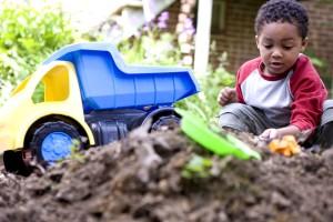 jeune, afro-américain, garçon, amusement, imaginaire, jeu, jouets, arrière-cour, de la saleté, pile