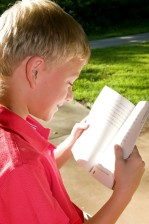young boy, photographed, reading, book, outdoors, setting