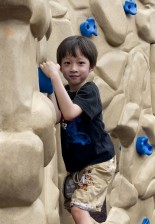 young boy, attempting, climb, fabricated, rock, wall