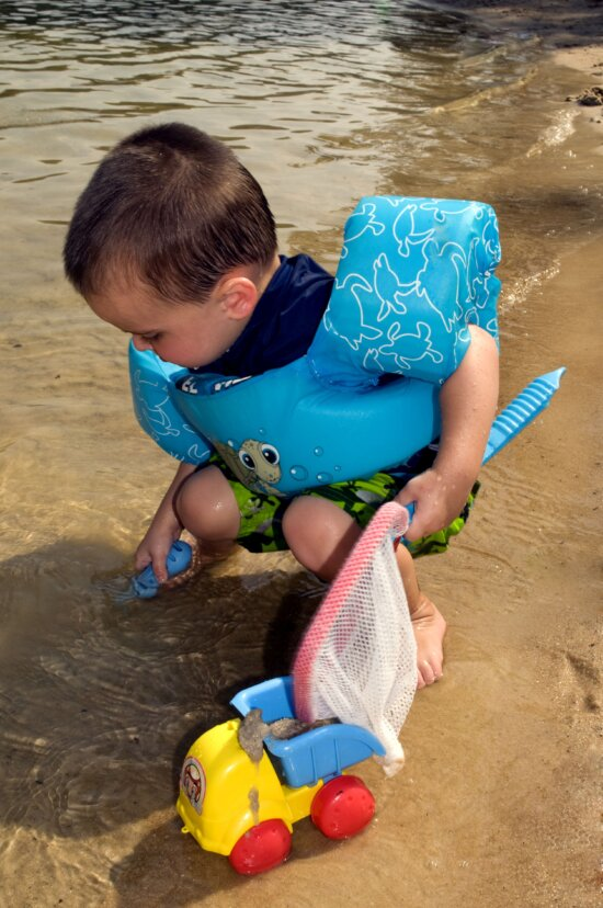 young boy, kneeling, beach, holding, toy, fishnet, hand, plastic, strainer, left