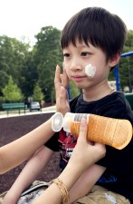 young boy, receiving, reapplication, coating, protective, sunscreen, mother