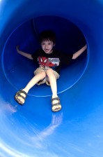 young boy, taking, trip, down, bright blue, slide, neighborhood, playground