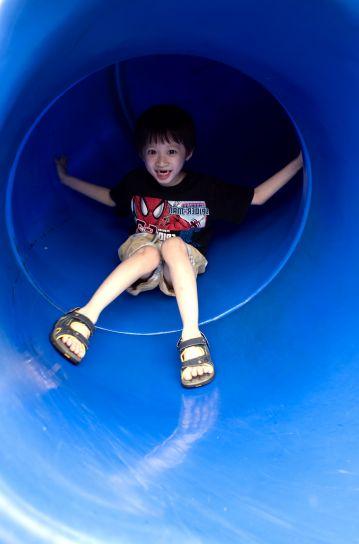 young boy, taking, trip, down, bright blue, slide, neighborhood, playground