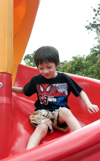 young boy, taking, trip, down, bright red, slide