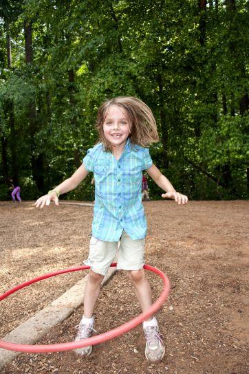 young, girl, having, fun, enjoying, time, spinning, hula, hoop, waist, schoolyard