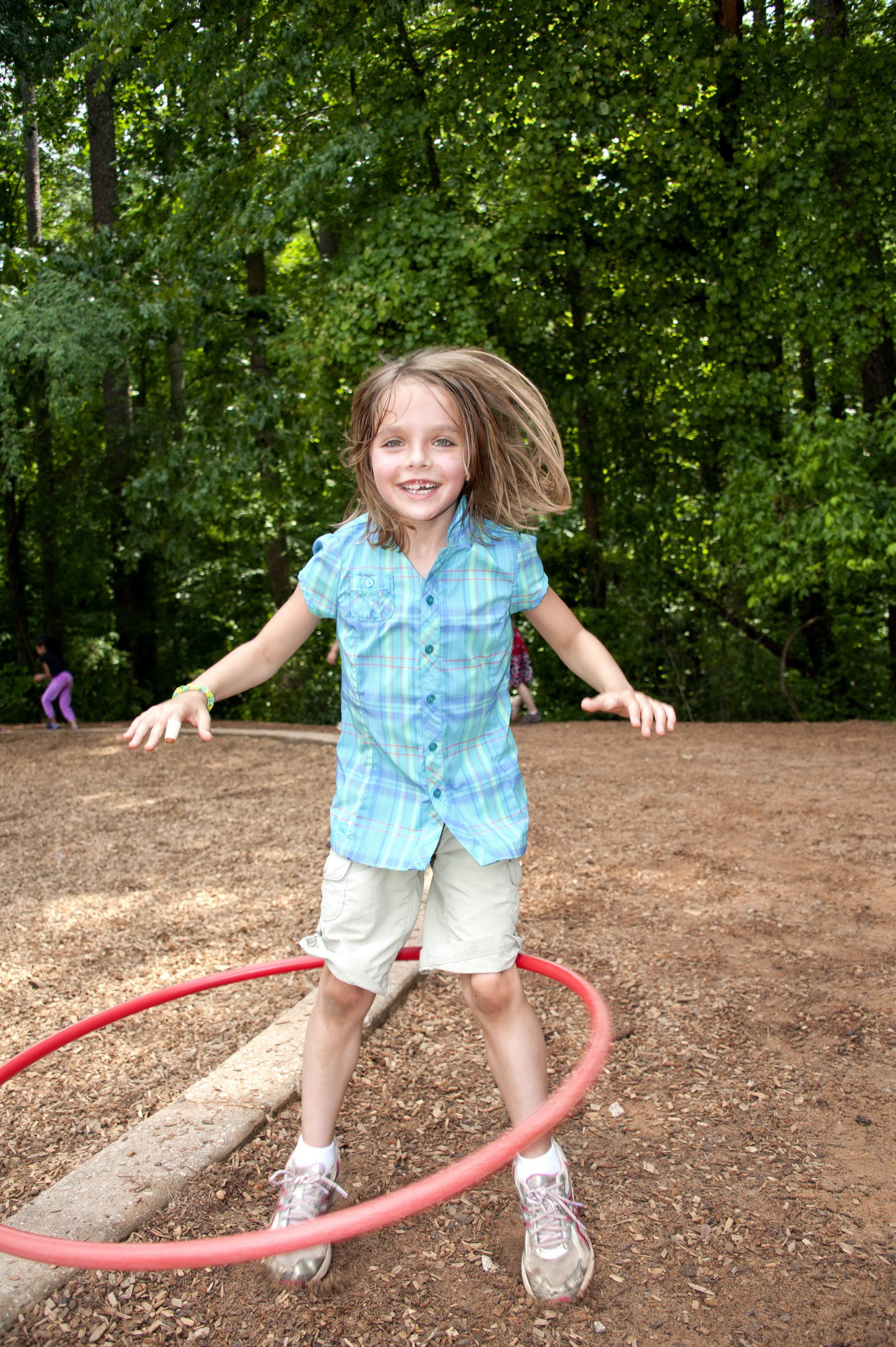 Free photograph; young, girl, having, fun, enjoying, time, spinning, hula, hoop, waist, schoolyard