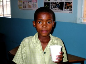 young, Namibian, boy enjoying, cup, nutritious, yogurt