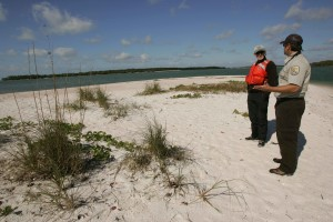 employee, white sand, beach, vegetation, speaking, visitor, orange, safety, vest