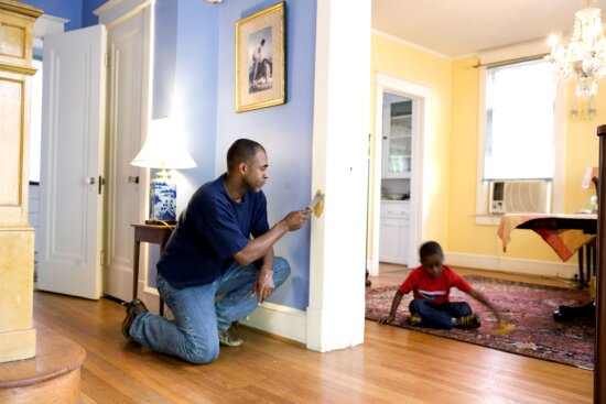father, repairing, interior, door, frame, young son, play, toy, car, adjacent, room