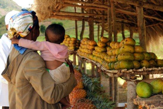 female, holding, child, arms, farmer, market, Farafangana, Madagascar
