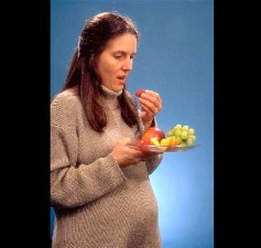 nutrition, pregnancy, pregnant, woman eating, strawberries, grapes, orange, slices, apple