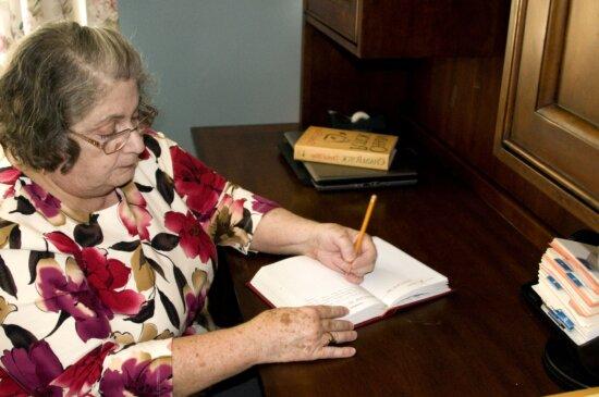older woman, writing, book