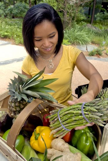 woman, adding, bunch, asparagus, stalks, woven, wooden, basket