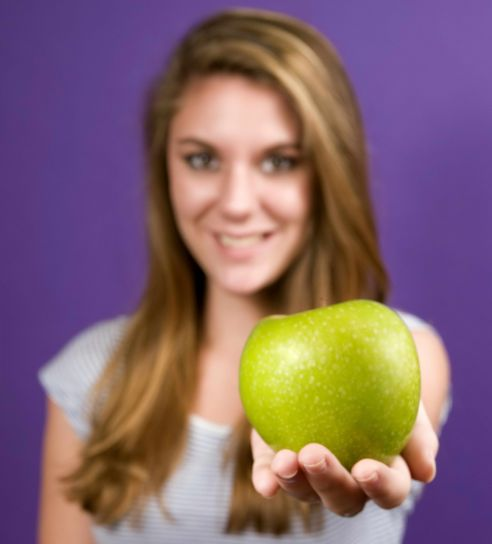 young, woman, extending, right, arm, holds, green, granny, smith, apple