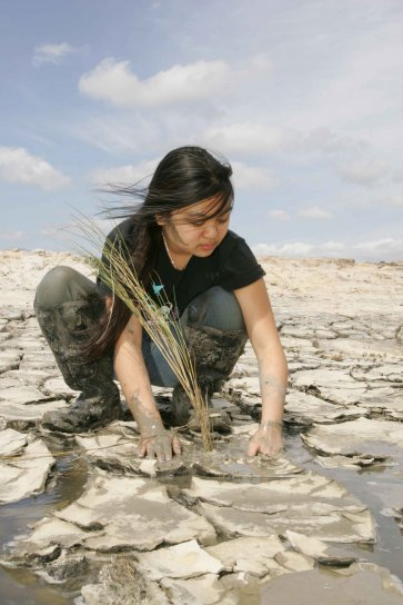 young woman, plants, marsh, grass, mud