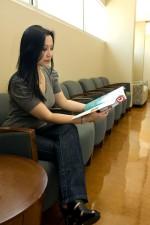 Молодая женщина, ожидание, чтение журнала, зал ожидания
