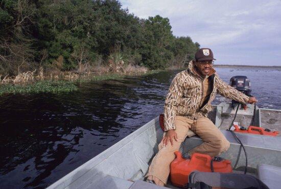Afro American men, employee, drives, small, motor, boat