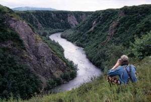 homme, assis, haut, colline, regarder, rivière, vers le bas