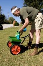 man, bent, filling, fertilizer, dispenser, fertilizer, granules