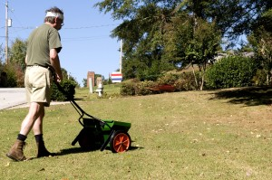man, dispensing, fertilizer, granules, front, lawn