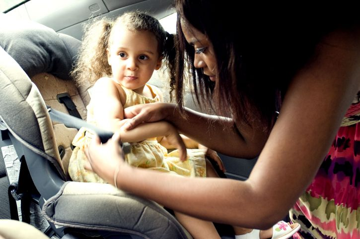 mother, securing, young, daughter, back, seat, car