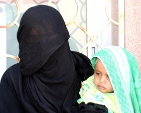 mother, young child, stand, outside, health care, facility, Yemen