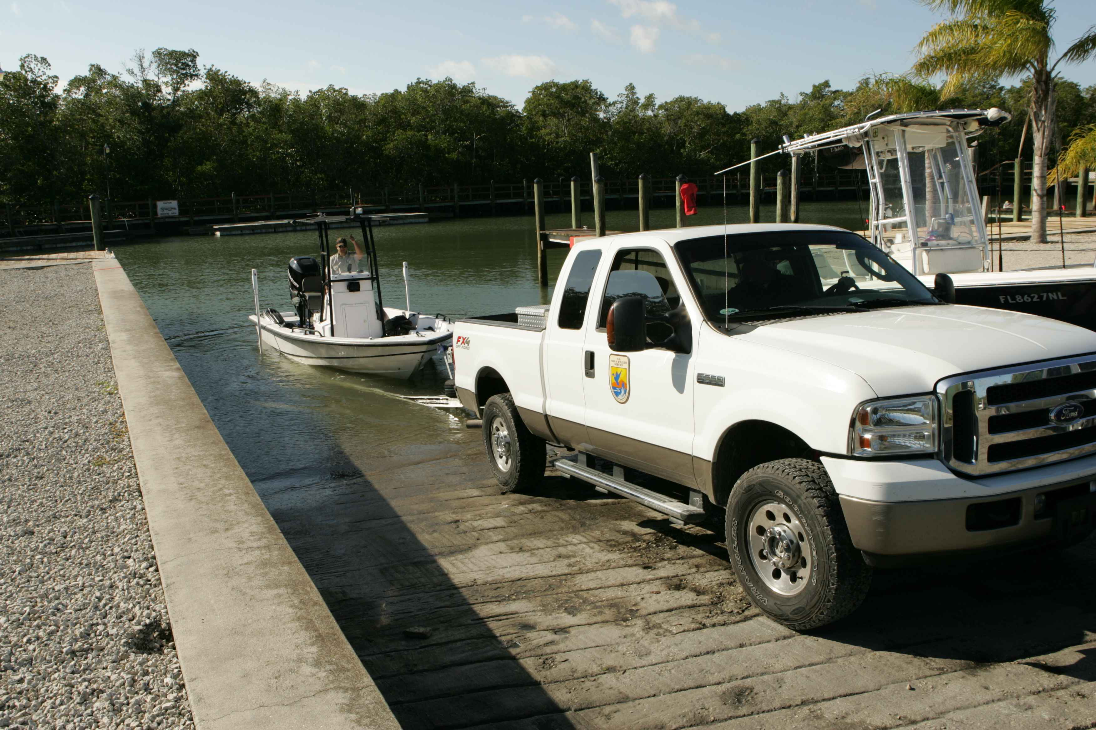 Two employees using pickup truck to put boat into water at boat ramp copyright friendly picture