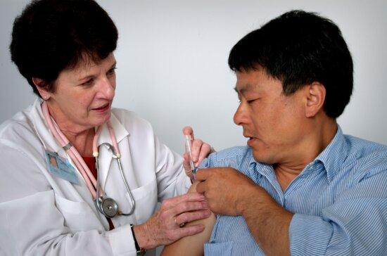 man, facilitating, procedure, lifting, sleeve, nurse, admistered, vaccine