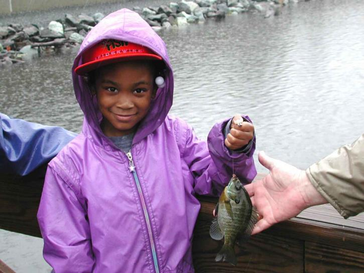 Mladi, African American, djevojka, osmijeh, držanje, ribolov, uhvatiti
