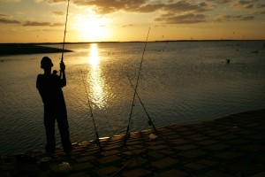 young man, stands, fishing, sunset