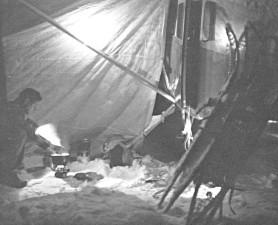 man, bending, cook, stove, outside, plane, night, tarp, protection
