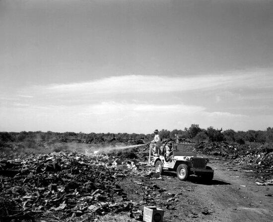 man, standing, back, jeep, spraying, fly, breeding, city, dump, Edinburg, Texas